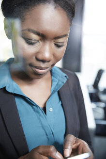 Germany, Neuss, Young Afro-european business woman using smart phone - STKF000865