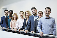 Germany, Neuss, Group of business people standing behind railing - STKF000786