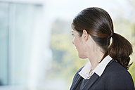 Germany, Neuss, Mature business woman looking out of window - STKF000870