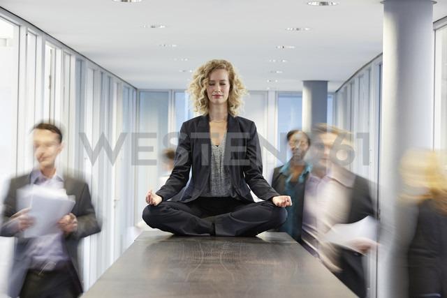 Germany, Neuss, Business woman meditating on desk - STKF000754 - Stefan Kranefeld/Westend61