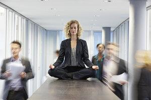 Germany, Neuss, Business woman meditating on desk - STKF000754