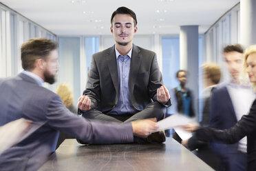 Germany, Neuss, Business man meditating on desk - STKF000748