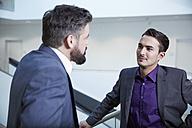 Germany, Neuss, Businessmen talking in corridor - STKF000722