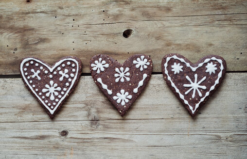 Three gingerbread hearts decorated with sugar icing on wooden table - CZF000126