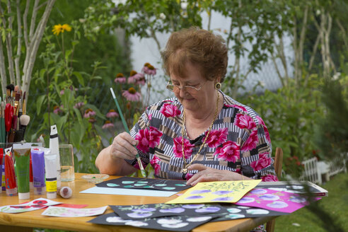 Germany, Bavaria, Ingolstadt, senior woman painting in garden - MABF000185