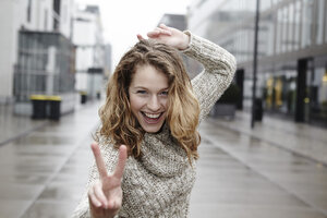 Portrait of happy young woman showing victory sign - FMKF000931