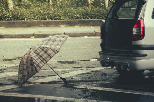 Brazil, Sao Paulo, Umbrella and car on the street - AMCF000006