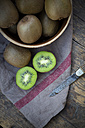 Bowl of kiwis (Actinidia deliciosa) and pocketknife on wooden table - LVF000380