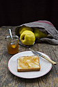 Quinces (Cydonia oblonga), selfmade quince jelly and slice of toast on wooden table - LVF000376