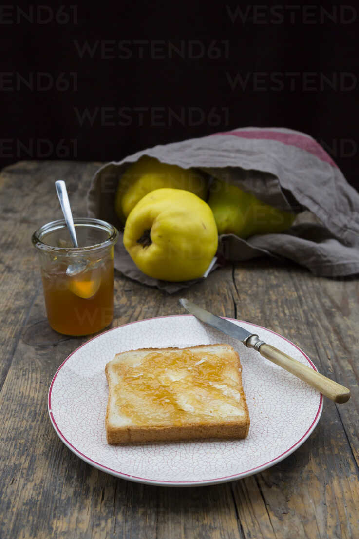 Quinces (Cydonia oblonga), selfmade quince jelly and slice of toast on wooden table - LVF000376 - Larissa Veronesi/Westend61