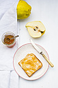Quinces (Cydonia oblonga), selfmade quince jelly and slice of toast on white wooden table - LVF000375