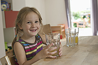 Smiling little girl sitting in the kitchen - CRF002528