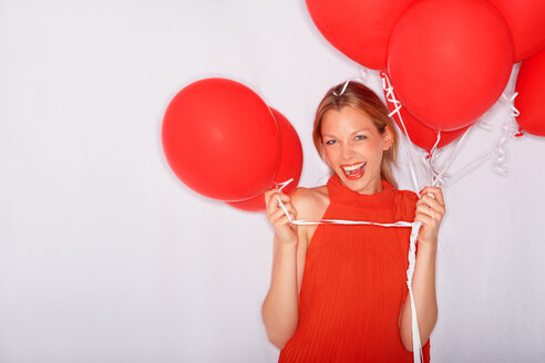 Excited young woman holding red balloons - CHAF000115