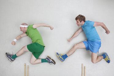 Two men jumping over hurdles - BAEF000675