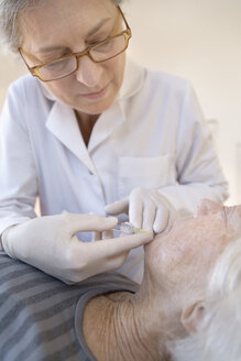 Female alternative practitioner giving senior woman injection acupuncture - TCF003735