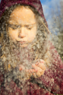 Portrait of girl blowing snow out of her hands - SARF000158