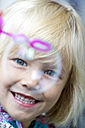 Portrait of smiling little girl with soap bubble - JFEF000244