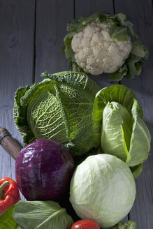 Cabbage varieties and antique knife on grey wooden table - CSF020578