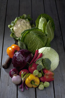 Cabbage varieties and other vegetables on grey wooden table - CSF020575