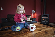 Little girl sitting on wooden table, testing smart phone - IPF000004