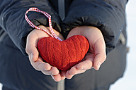 Hands holding red knitted heart, close-up - LB000443
