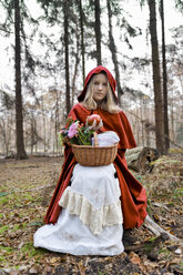 Girl masquerade as Red Riding Hood sitting on a trunk in the wood - CLPF000043