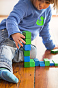 Little girl playing with blue aund green wooden building bricks - LVF000395