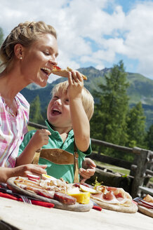 Austria, Salzburg State, Altenmarkt-Zauchensee, mother and son having an alpine picnic - HHF004722
