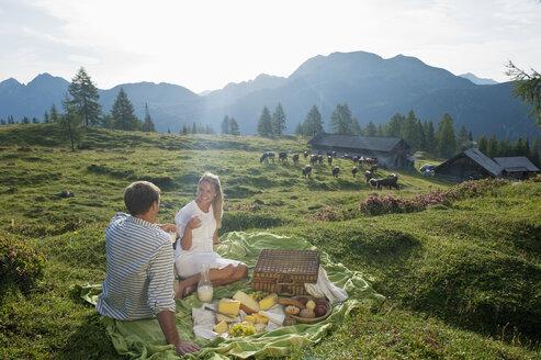 Austria, Salzburg State, Altenmarkt-Zauchensee, couple having a picnic on alpine meadow - HHF004719