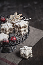With powdered sugar sprinkled star-shaped cinnamon cookies and red Christmas baubles on cake stand - SBDF000373