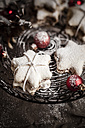 With powdered sugar sprinkled star-shaped cinnamon cookies and red Christmas baubles on cake stand - SBDF000375
