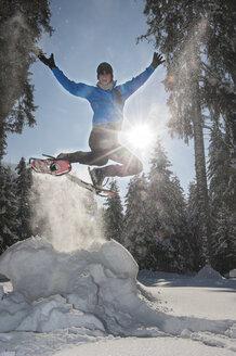 Austria, Salzburg State, Altenmarkt-Zauchensee, Man with snowshoes jumping in winter landscape - HHF004693