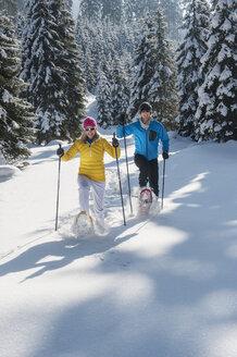 Austria, Salzburg State, Altenmarkt-Zauchensee, Couple snowshoeing in winter landscape - HHF004675