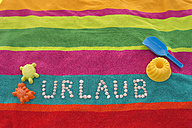 The word 'Urlaub' formed by shells lying between sand toys on a multicolored bath towel - ASF005262