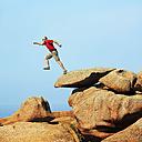 France, Bretagne, Tregastel, Man jumping on rocks - BIF000219