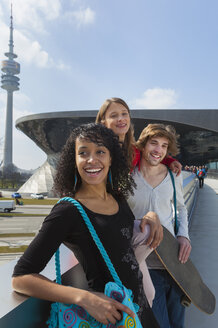Germany, Bavaria, Munich, Three friends having fun at the Olympic Park - HSI000302