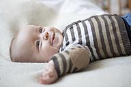 Portrait of happy baby boy lying on blanket - RBF001604