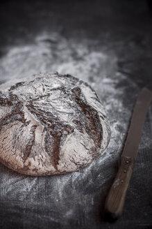 Rye-Spelt-Malt loaf, flour and bread knife on wooden table - SBDF000427
