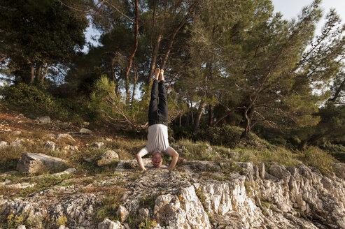 Croatian, Vrsar, Man doing yoga on beach, Shirshasana - KJ000281