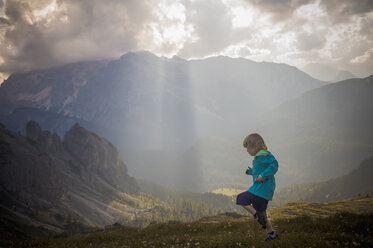 Italy, Province of Belluno, Veneto, Auronzo di Cadore, little boy running on alpine meadow near Tre Cime di Lavaredo - MJF000470