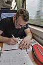 Young man working on maths problems on the train - LA000396