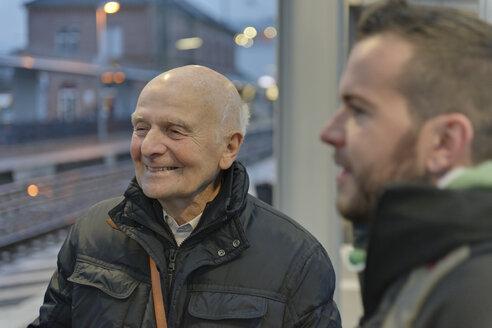 Young man and senior man waiting together at platform - LA000397