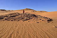 Algeria, Sahara, Tassili N'Ajjer National Park, Woman walking in the dunes of In Tehak - ES000908