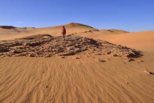 Algeria, Sahara, Tassili N'Ajjer National Park, Woman walking in the dunes of In Tehak - ES000908