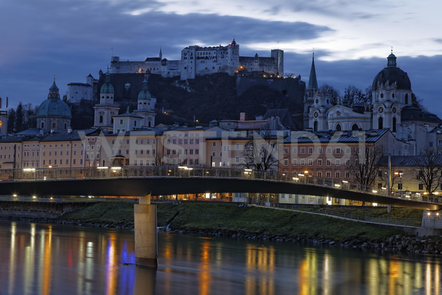 Austria, Salzburg State, Salzburg, fortress Hohensalzburg with old town and towers of Salzburg Cathedral, Salzach River, right collegiate church, in the evening - GF000340