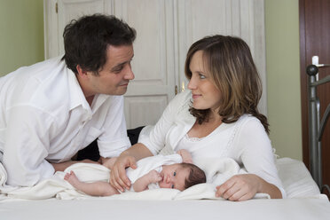 Parents with newborn baby girl lying on bed - PA000201