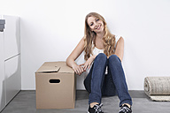 Smiling young woman with cardboard box - PDF000605