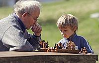 Germany, Rhineland-Palatinate, Leutesdorf, grandfather and grandson playing chess - PAF000258