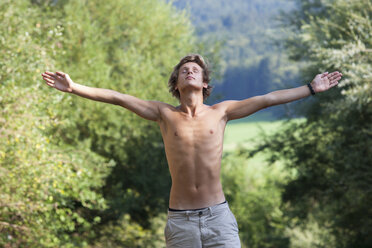 Austria, Salzkammergut, Mondsee, portrait of young man with outstretched arms - WWF003198
