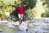 Austria, Salzkammergut, Mondsee, young man crossing a brook - WWF003200
